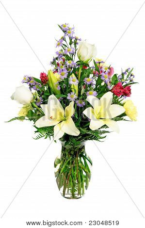 Colorful flower arrangement centerpiece in glass vase with roses, daisies and lilies
