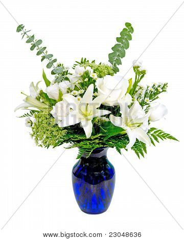 White and green flower arrangement centerpiece in blue vase with lilies isolated on white