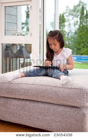 A young child playing with a digital tablet in a living room interior