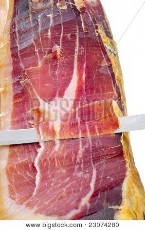 closeup of a knife cutting spanish serrano ham