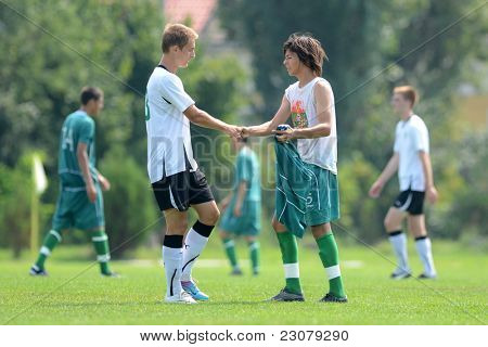 KAPOSVAR, HUNGARY - AUGUST 27: Competitors shake hands after the Hungarian National Championship under 18 game between Kaposvar (green) and Gyor (white) August 27, 2011 in Kaposvar, Hungary.