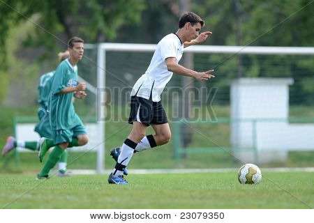 KAPOSVAR, HUNGARY - AUGUST 27: Peter Bokor (in white 2) in action at the Hungarian National Championship under 18 game between Kaposvar (green) and Gyor (white) August 27, 2011 in Kaposvar, Hungary.