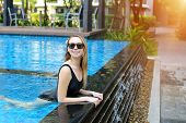 Young Woman Relax In Swimming Pool, Looking At Camera Wearing Sunglassses And Enjoy Weather In Tropi poster