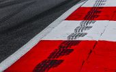 Asphalt Red And White Kerb Of A Race Track Detail With Tire Marks poster