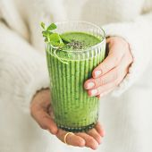 Matcha Green Vegan Smoothie With Chia Seeds And Mint In Glass In Hands Of Female Wearing White Sweat poster