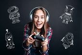 Funny Game. Positive Excited Young Woman Feeling Happy While Sitting With A Modern Game Console And  poster