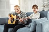Future Guitar Player. Handsome Alert Well-built Man Holding The Guitar And Teaching His Son To Play  poster