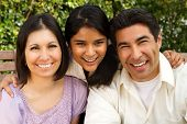 Hispanic Family With A Teen Daughter Sitting Outside. poster