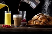 Table Breakfast. Fresh Hot Croissants, Pouring Orange Juice, Pouring Coffee Into Milk. Ripe Berries poster