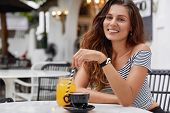 Satisfied Young Woman With Pleasant Appearance Recreats At Coffee Shop, Happy To Spend Summer Holida poster