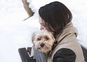 Young Brunette Woman Sitting On A Bench, Surrounded By Snow, Holding Her Havanese Bichon Dog With Af poster
