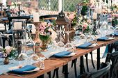 Wedding Or Other Catered Event Setting, Flowers, Candles, White Plates, Blue Napkins, Wooden Tables, poster