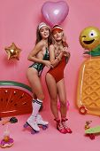 Girls With Style. Full Length Of Two Attractive Young Women In Swimwear Looking At Camera And Smilin poster