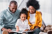 Happy African American Daughter Reading For Parents At Home poster