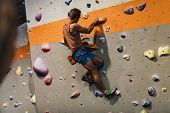 Man Climbing Indoor Boulder Wall poster
