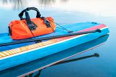 waterproof duffel on a deck of stand up paddleboard - paddling expedition concept poster