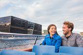 Copenhagen tourists couple on city boat cruise tour enjoying view of the black diamond Royal library poster