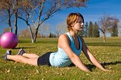 picture of hottie  - Woman laying on grass doing a back extension - JPG
