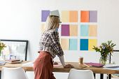 Rear View Of Fashion Magazine Editor Working In Modern Office With Color Palette On Wall poster