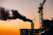 Atmospheric Air Pollution From Industrial Smoke. Crane And Building Construction Site With Pipe With poster