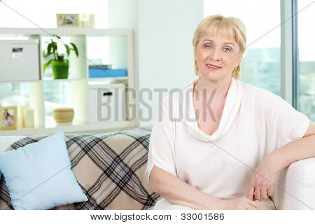 Portrait of friendly aged woman looking at camera