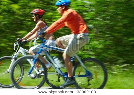 Image in motion of two bicyclists riding down country road