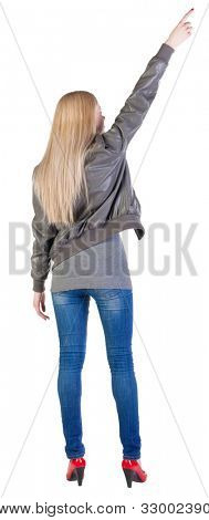 Back view of young blonde woman pointing at wall . beautiful girl in jeans and red kitten heels. Rear view people collection.  backside view of person.  Isolated over white background