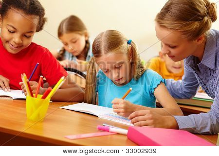 Portrait of teacher looking at a drawing schoolgirl�?�¢??s copybook at lesson