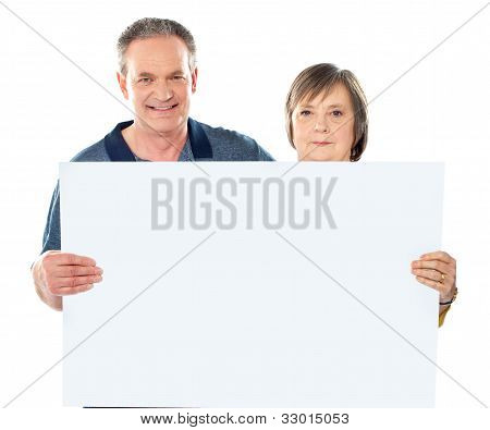 Smiling Aged Couple Displaying Blank Banner