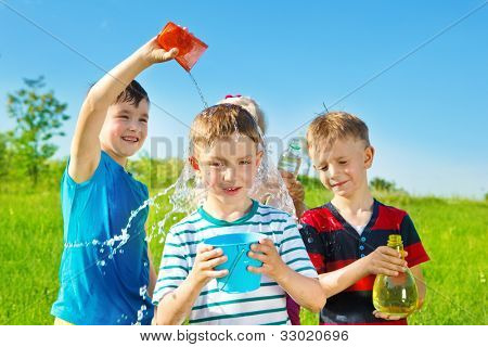 Children playing with water in summer park
