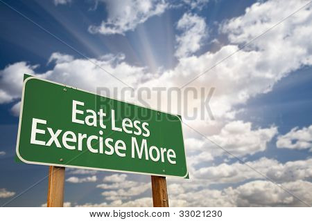 Eat Less Exercise More Green Road Sign with Dramatic Clouds, Sun Rays and Sky.