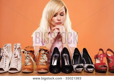 Fashion conscious woman looking at a row of different shoes trying to choose accessories for her outfit