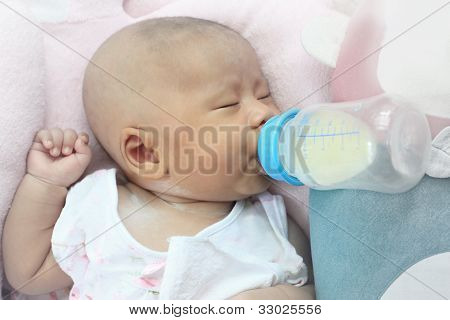 face of infant  drinking mother milk from bottle