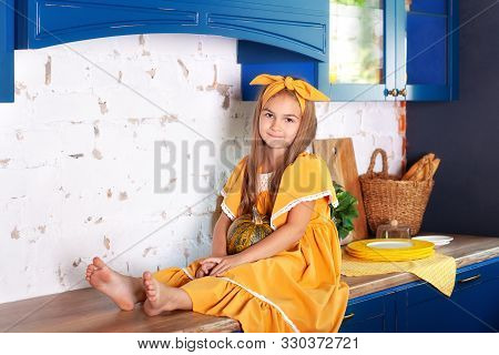 poster of Little Girl Sitting On Work Surface Of Kitchen Waiting For Breakfast. Cheerful And Mischievous Girl