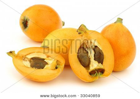 fresh loquat fruit (Eriobotrya japonica) and a cut one on a white background