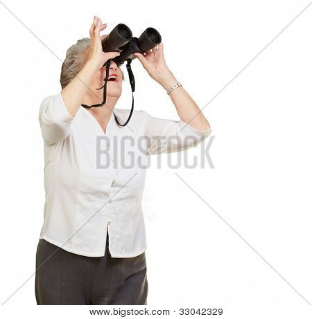 portrait of a senior woman looking through binoculars over a white background