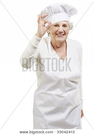 senior woman cook doing an excellent symbol against a white background