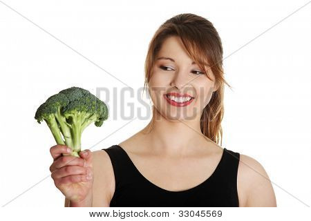 Happy young woman shoving broccoli