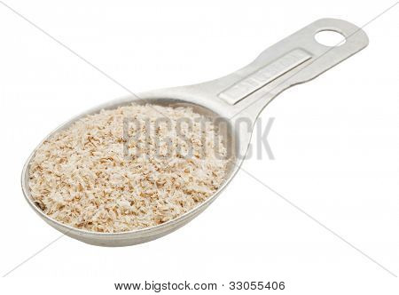 psyllium seed husks - dietary supplement, source of soluble fiber, on a n old aluminum measuring tablespoon