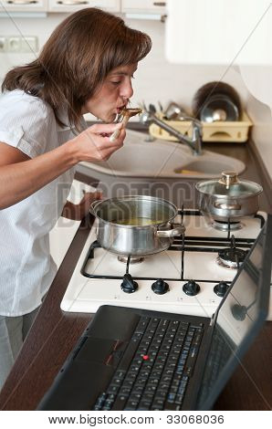 Multitasking woman - cooking meal and working