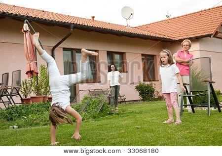 Children doing cartwheels in backyard