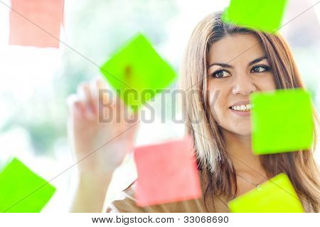 Beautiful business woman multitasking with lots of post-its