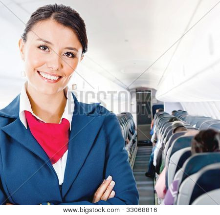 Beautiful flight attendant in an airplane smiling