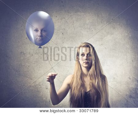 Pretty young woman holding a balloon with her face on it