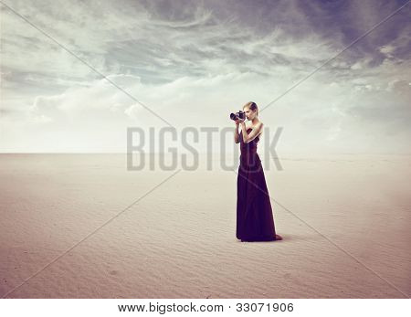 Beautiful elegant woman holding a camera