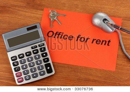 Inserieren Sie Vermietungsbüro auf rotes Papier auf Holz Hintergrund