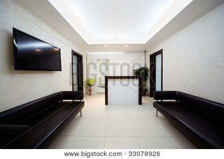 Hallway in the beauty salon with two black leather divans and big TV panel on the wall.