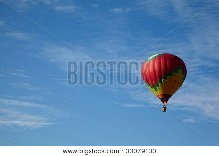 Many-colored hot air balloon with people fly in the blue sky.