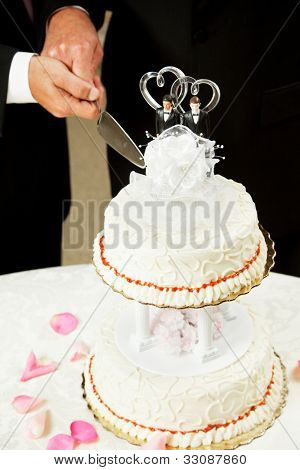 Closeup of a wedding cake topped with two grooms, being cut by two men's hands.