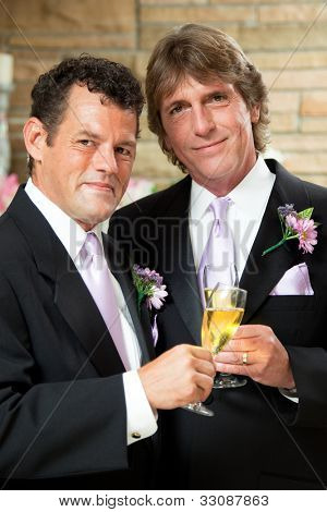 Handsome gay couple give champagne toast at their wedding reception.